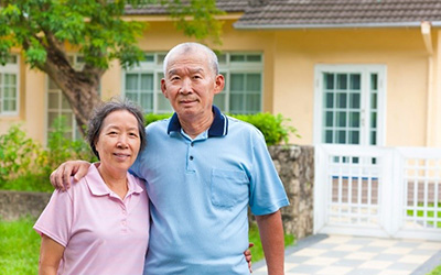 Asian couple standing in front of a yellow house