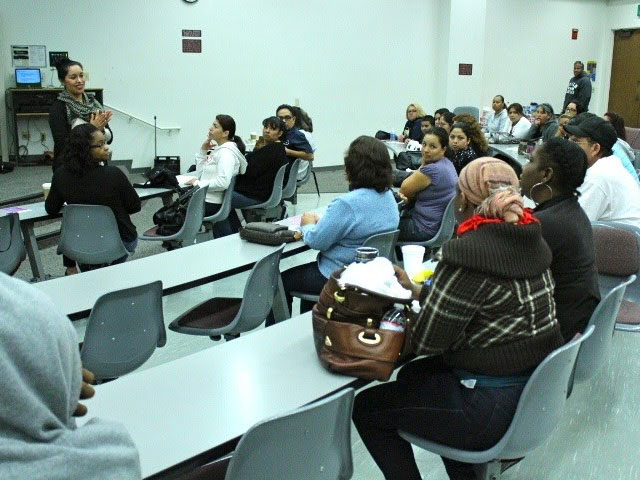 woman speaking to a full classroom of adults